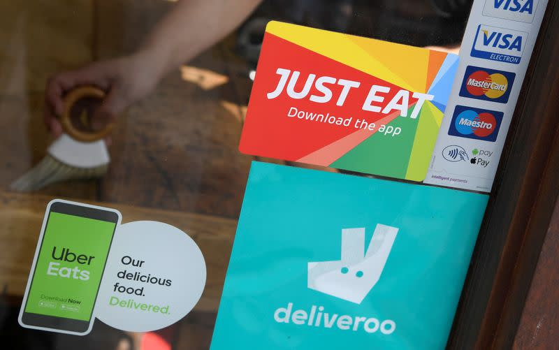 FILE PHOTO: Signage for Just Eat is seen next to Uber Eats and Deliveroo advertisements on the window of a restaurant in London