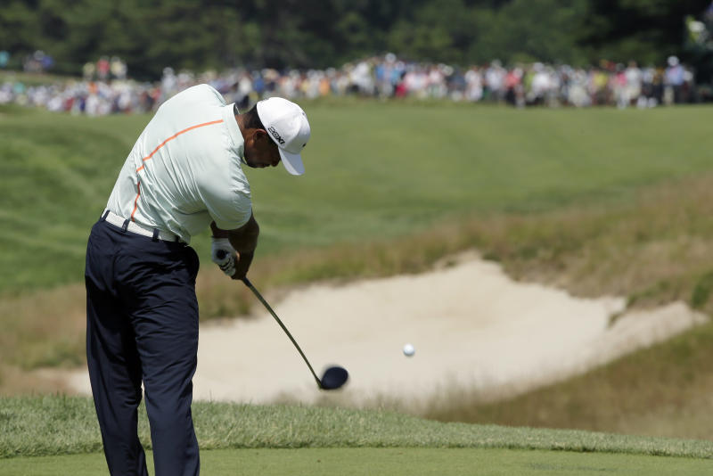 Tiger Woods tees off on the fourth hole during the third round of the U.S. Open golf tournament at Merion Golf Club, Saturday, June 15, 2013, in Ardmore, Pa. (AP Photo/Charlie Riedel)