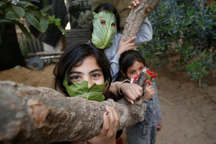 Palestinian children pose with makeshifts masks made of cabbage while cooking at home with their family in Beit Lahia in the northern Gaza Strip on April 16, 2020 amid the coronavirus COVID-19 pandemic. (AFP Photo/MOHAMMED ABED)