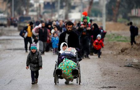 Displaced Iraqi people from different areas in Mosul flee their homes after clashes to reach safe areas, as Iraqi forces battle with Islamic State militants in the city of Mosul