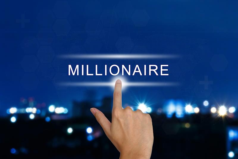 A finger pointing at the word millionaire and in the background blurry lights of a city.