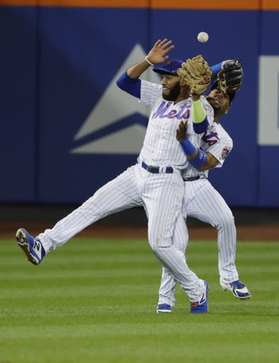 New York Mets' Amed Rosario (1) and Dominic Smith (22) collide while trying to catch a ball hit by San Francisco Giants' Brandon Crawford during the thirteenth inning of a baseball game Monday, Aug. 20, 2018, in New York. Andrew McCutchen scored on the error by Smith. (AP Photo/Frank Franklin II)