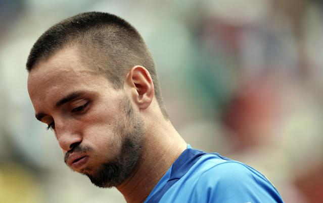 FILE - In this June 2, 2013, file photo, Serbia's Viktor Troicki blows out air as he plays France's Jo-Wilfried Tsonga during their fourth round match of the French Open tennis tournament at the Roland Garros stadium in Paris. Troicki's doping ban was reduced from 18 months to 12 on Tuesday, Nov. 5, 2013 although he still cannot play in next week's Davis Cup final. (AP Photo/Christophe Ena, File)