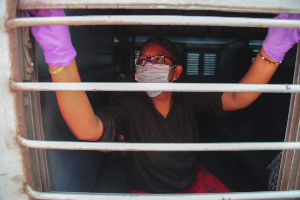 An Indian passenger wearing face mask and gloves as a precaution against COVID-19 opens glass window of a train compartment at Secunderabad Railway Station in Hyderabad, India, Saturday, March 21, 2020. For most people, the new coronavirus causes only mild or moderate symptoms. For some it can cause more severe illness. (AP Photo/Mahesh Kumar A.)