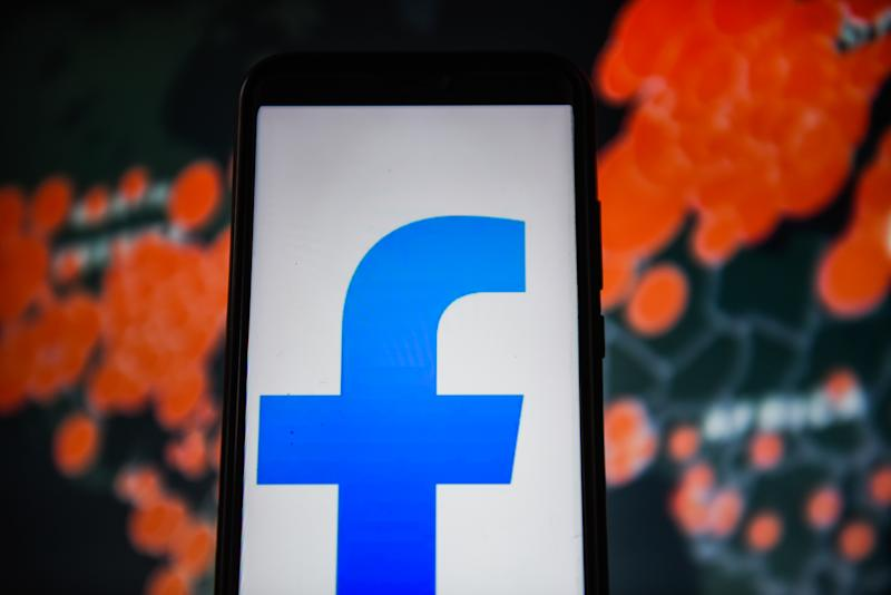 POLAND - 2020/04/01: In this photo illustration a Facebook Lite logo is seen displayed on a smartphone with a World map of COVID 19 epidemic on the background. (Photo Illustration by Omar Marques/SOPA Images/LightRocket via Getty Images)