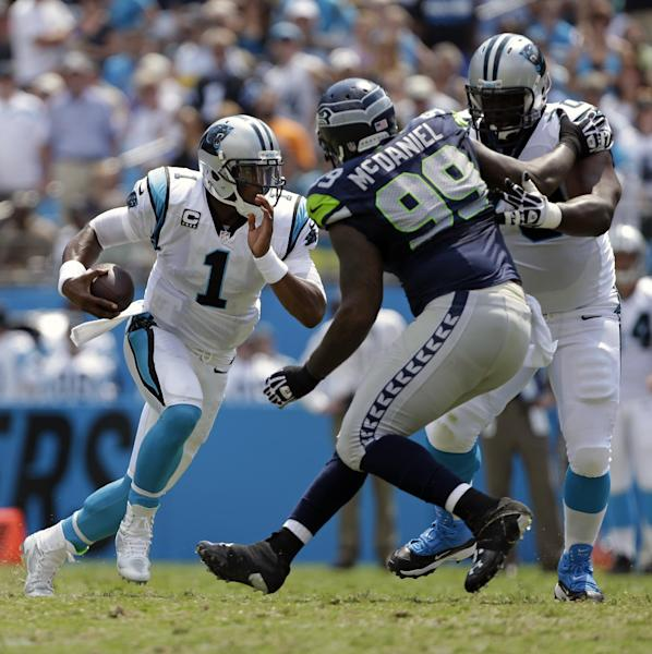 Carolina Panthers quarterback Cam Newton (1) runs past Seattle Seahawks defensive tackle Tony McDaniel (99) being blocked by Carolina Panthers' Edmund Kugbila (70) during the first half of an NFL football game in Charlotte, N.C., Sunday, Sept. 8, 2013. (AP Photo/Bob Leverone)
