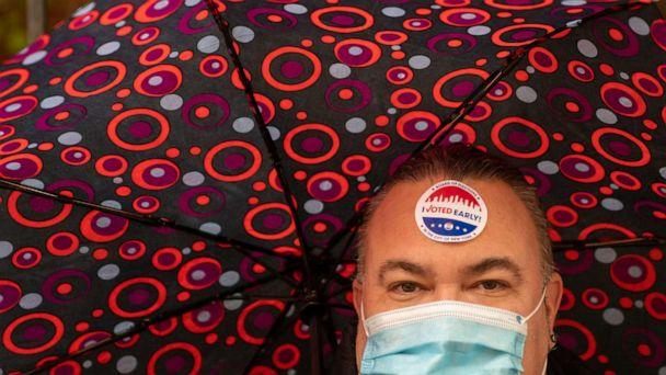 PHOTO: A person carries an umbrella and wears a mask at a polling station in Hunter-Bellevue School of Nursing on Nov. 1, 2020, in New York. (David Dee Delgado/Getty Images)