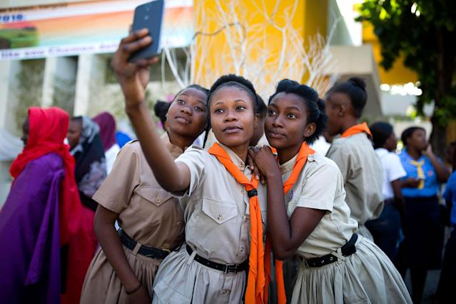 <p>Girl scouts pose for a group photo at the third station of the Way of the Cross reenactment marking Good Friday, in Port-au-Prince, Haiti, Friday, March 30, 2018. Thousands of Haitians are commemorating the crucifixion of Jesus Christ by reenacting the Way of the Cross, visiting the 14 stations, each marking an event that befell Jesus Christ on his final journey. (Photo: Dieu Nalio Chery/AP) </p>