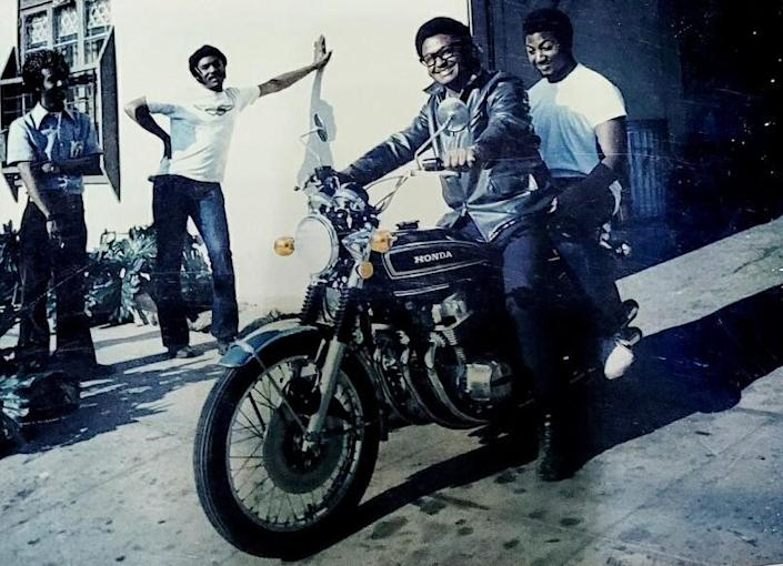 A father and son smile on a Honda motorcycle in a driveway