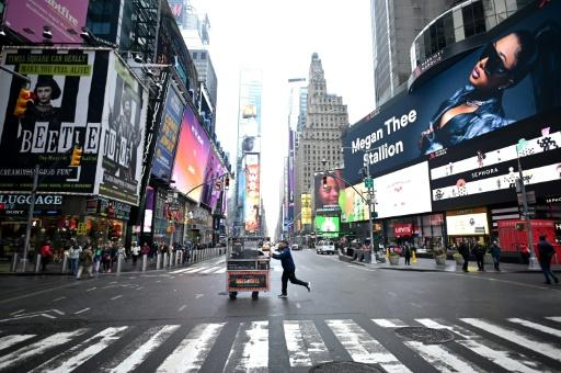 A food vendor pushes his cart across an emptier than usual Times Square on March 13