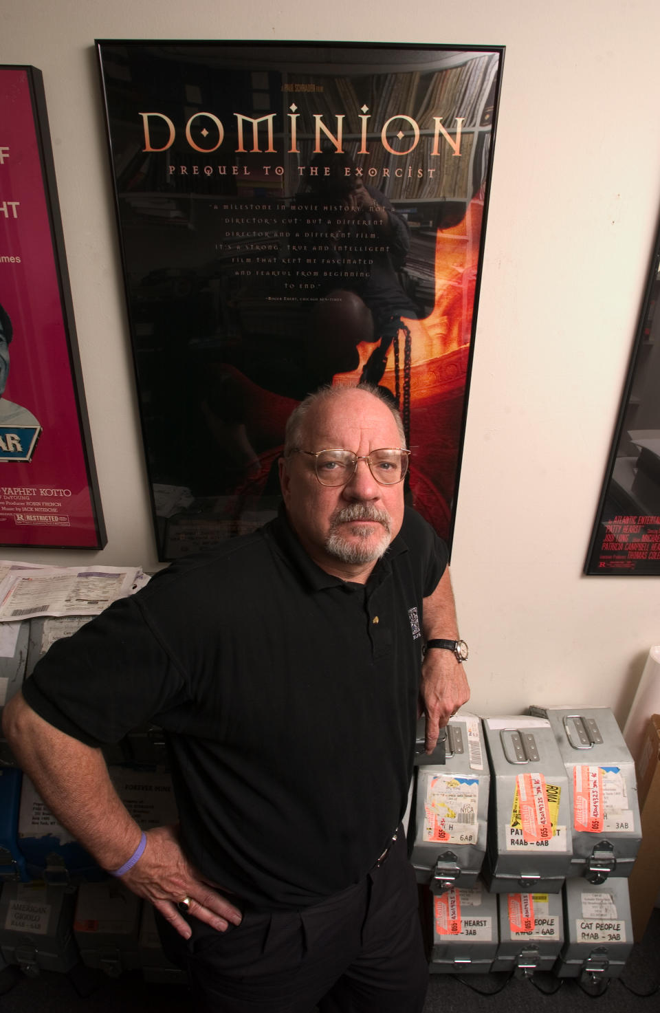 """Director and screenwriter Paul Schrader is photographed  in his New York office May 17, 2005, with a poster for his film """"Dominion Prequel to the Exorcist"""" on the wall behind him.  (AP Photo/Jim Cooper)"""