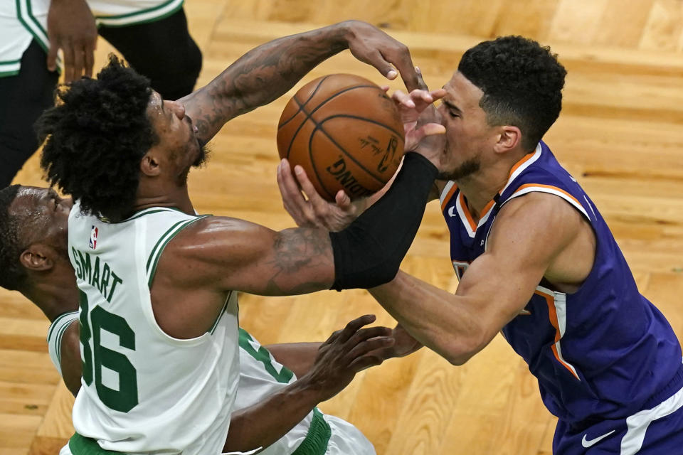 Boston Celtics guard Marcus Smart (36) and Phoenix Suns guard Devin Booker (1) compete for the ball in the first half of an NBA basketball game, Thursday, April 22, 2021, in Boston. (AP Photo/Elise Amendola)