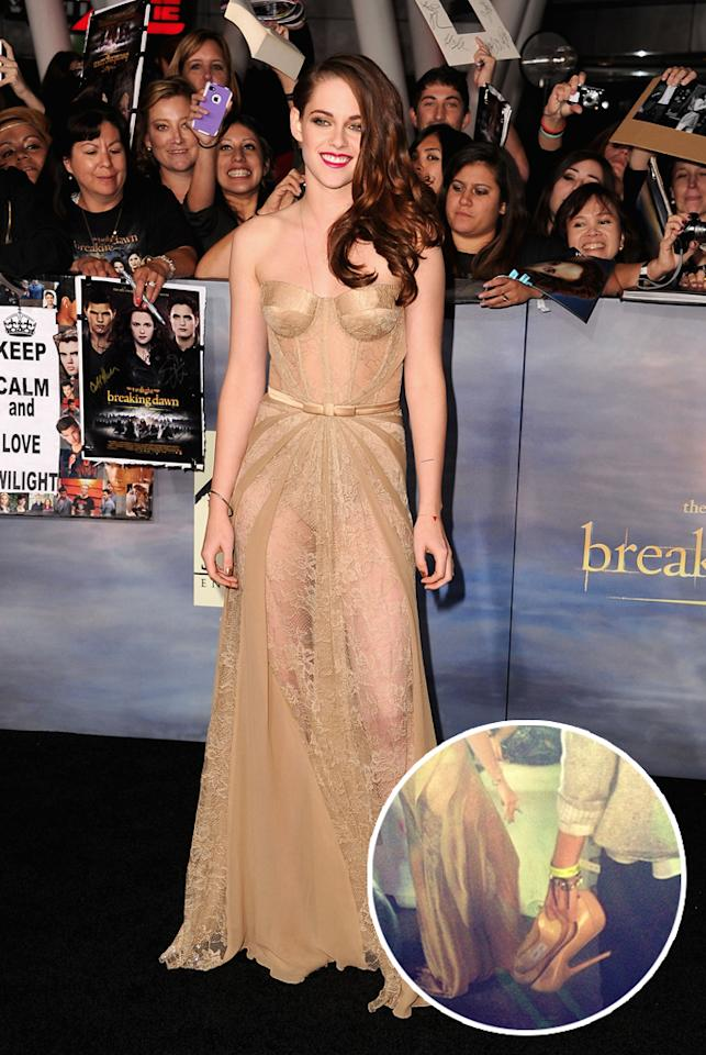 "Wearing a surprisingly see-through gold lace dress, Kristen Stewart got comfortable with her fans and went barefoot as she signed autographs at the world premiere of ""The Twilight Saga: Breaking Dawn – Part 2"" in Los Angeles on Monday evening. Stewart slipped on her Jimmy Choo shoes before she walked the carpet, but admitted she was ""already looking forward to taking them off."" She told Yahoo! that she didn't know what she was wearing, but her stylist shared that Zuhair Murad designed the pale strapless gown. (Photo by WireImage, insert courtesy @YahooMovies/Twitter)"