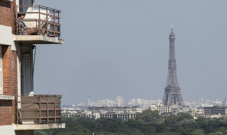 A woman enjoys the sun on her balcony as the Eiffel Tower is clearly seen in the background