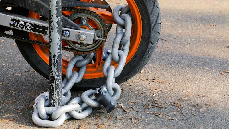 Motorcycle anti-theft chain with padlock on rear wheel