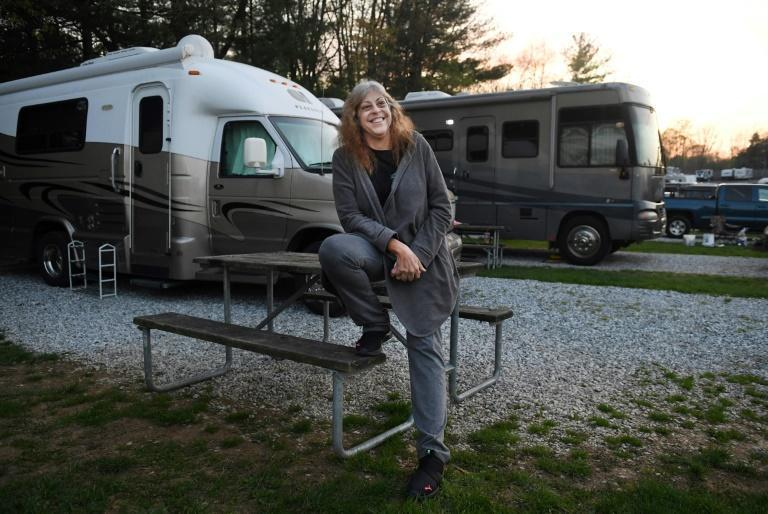 """Kathy Wardell, who lives fulltime on the road, poses outside her RV that she named """"Howy,: short for """"Home on Wheels, Yay!"""""""