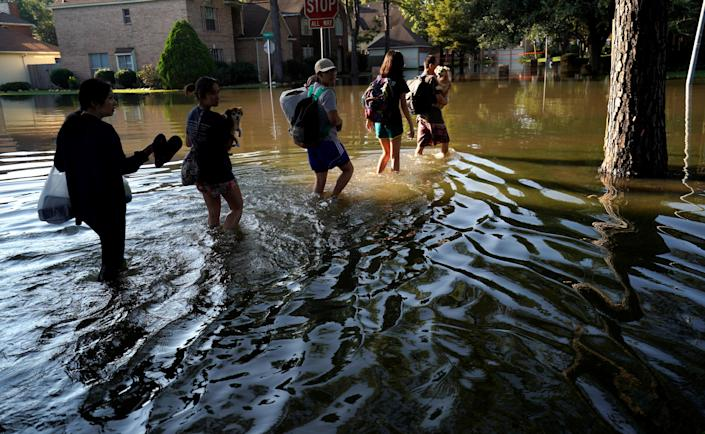 <p>Members of the Nguyen family return to their home for the first time since Harvey floodwaters arrived in north western Houston, Texas, Aug. 31, 2017. (Photo: Rick Wilking/Reuters) </p>