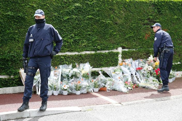 Police officers stand in front of flowers laid, on June 15, 2016, outside the house in Magnanville where a man claiming allegiance to the Islamic State group killed a French policeman and his partner on the night of June 13 (AFP Photo/Matthieu Alexandre)