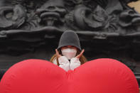 A visitor wearing a mask to protect from the coronavirus poses for photos near a heart shaped balloon displayed at a mall district during the second day of the Chinese Lunar New Year in Beijing on Saturday, Feb. 13, 2021. (AP Photo/Ng Han Guan)