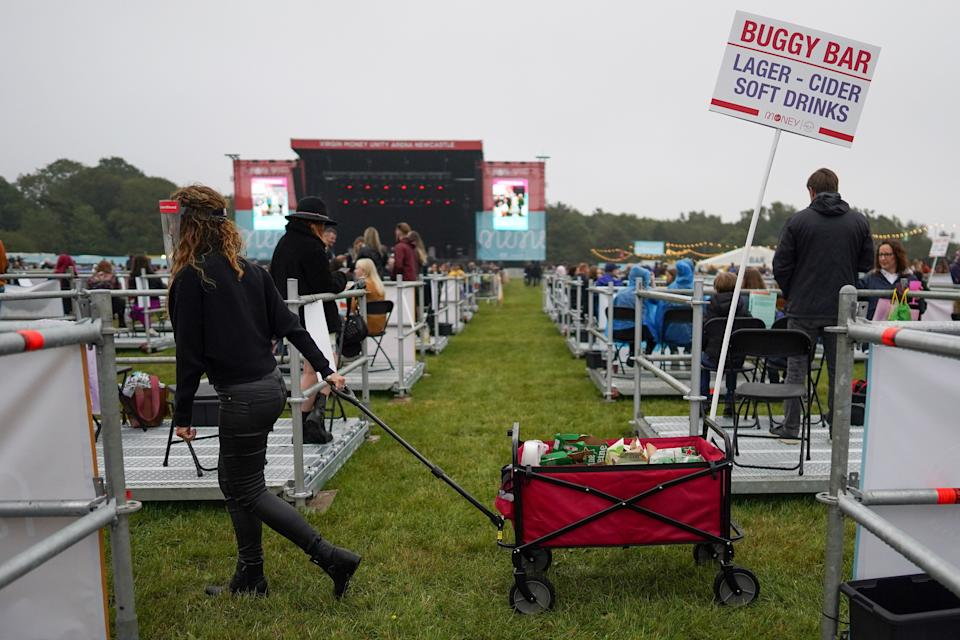 An employee wheels a mobile drink trolley between socially distanced enclosures ahead of Sam Fender performing at the Virgin Money Unity Arena on Aug. 13 in Newcastle upon Tyne, England. Sam Fender is the first to perform at the socially distanced music venue. (Photo: Ian Forsyth via Getty Images)