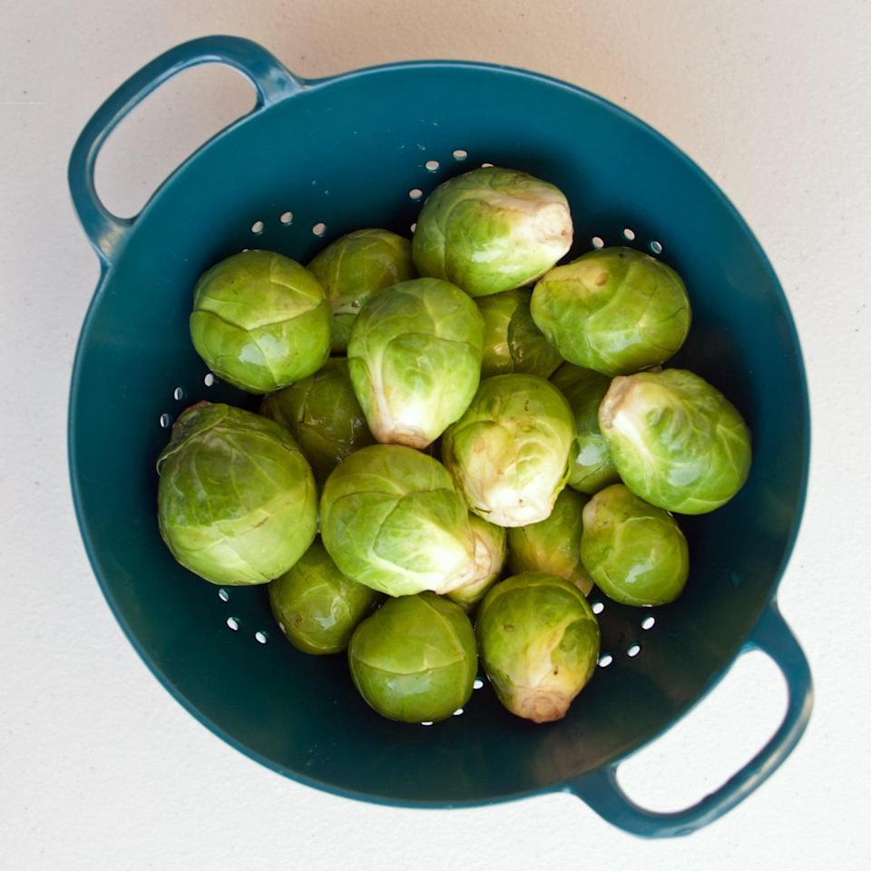 <p>If your brussels sprouts are still attached to a stalk, then snap them off. Then give them a quick rinse to remove any surface dirt. </p>