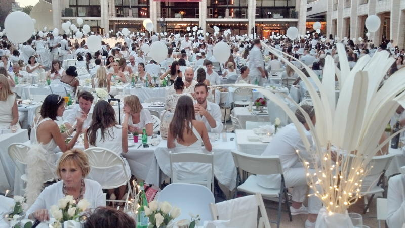 An estimated 3,000 people all dressed in white attend a flash mob feast on Monday, Aug. 20, 2012 at the Lincoln Center for the Performing Arts in New York.  The venue was a secret until just before the dinner started at 7 p.m. when registered guests got emails telling them where to go.  (AP Photo/Verena Dobnik)