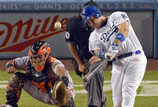Los Angeles Dodgers' A.J. Ellis, right, hits a two-run home run as San Francisco Giants catcher Hector Sanchez catches during the seventh inning of their baseball game, Tuesday, Oct. 2, 2012, in Los Angeles. (AP Photo/Mark J. Terrill)