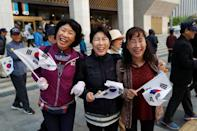 Supporters hold South Korean flags while waiting for a convoy transporting South Korean President Moon Jae-in to leave the Presidential Blue House for the inter-Korean summit, in Seoul, South Korea, April 27, 2018.