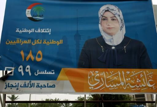 """A picture taken on May 8, 2018 in Baghdad shows an electoral campaign billboard of Aisha al-Massari, proudly boasting that she has """"accomplished 1,000 deeds"""""""