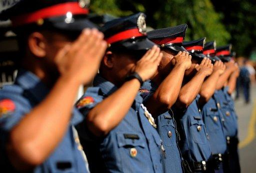 Philippine police officers salute as they stand at attention at the Philippine National Police headquarters in Manila