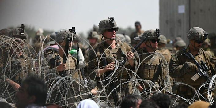 US soldiers stand guard behind barbed wire as Afghans sit on a roadside near the military part of the airport in Kabul on August 20, 2021, hoping to flee from the country after the Taliban's military takeover of Afghanistan