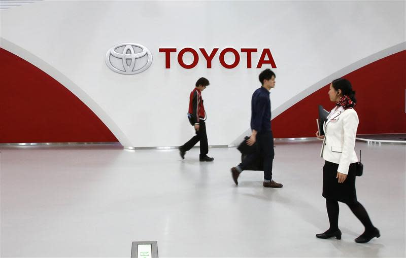 File photo shows employees and customer walking in front of Toyota Motor's logo at the company's showroom in Tokyo