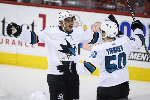 San Jose Sharks left wing Evander Kane (9) celebrates his fourth goal with center Chris Tierney (50) during the third period of an NHL hockey game against Calgary Flames on Friday, March 16, 2018, in Calgary, Alberta. (Jeff McIntosh/The Canadian Press via AP)