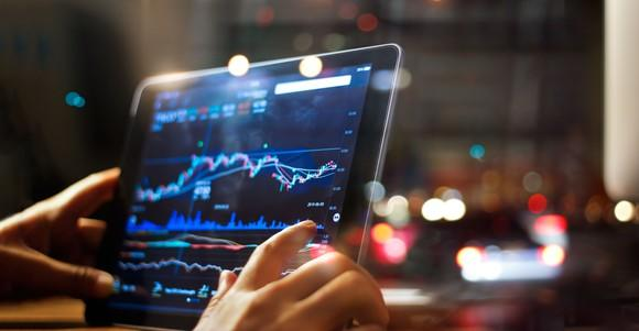 A pair of hands holding a tablet with stock charts on it.