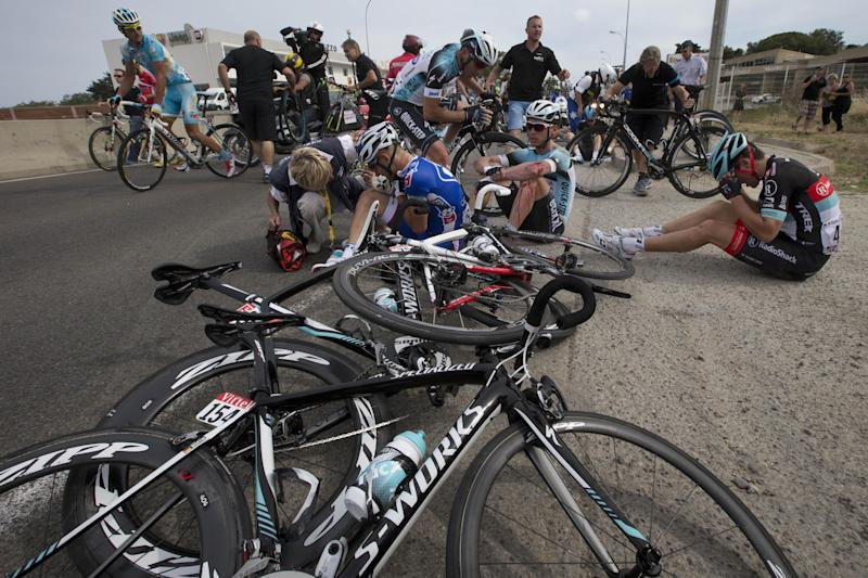 Murilo Antoniobil Fischer of Brazil, center left, Tony Martin of Germany, center right, and Tony Gallopin of France, right, wait for medical assistance after crashing in the last kilometers of the first stage of the Tour de France cycling race over 213 kilometers (133 miles) with start in Porto Vecchio and finish in Bastia, Corsica island, France, Saturday June 29, 2013. (AP Photo/Joel Saget, POOL)