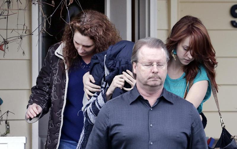 ADDS STATEMENT FROM KNOX SPOKESMAN DAVID MARRIOTT-An unidentified woman, center, is hidden under a jacket while being escorted from the home of Amanda Knox's mother, Thursday, Jan. 30, 2014, in Seattle.  Knox's family spokesman, David Marriott, said Thursday that Knox was at the house when an Italian court upholding her murder conviction was read Thursday, but said he didn't know whether the person who emerged was Knox. On Friday, Marriott stated he had made inquiries and that the person under the jacket wasn't Knox. (AP Photo)