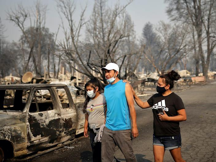 "Sandra and Daniela Reyes comfort Isaias Reyes while visiting their damaged trailer home after the wildfires destroyed a neighborhood in Bear Creek, Phoenix, Oregon, U.S., September 10, 2020. <p class=""copyright"">Carlos Barria/REUTERS</p>"