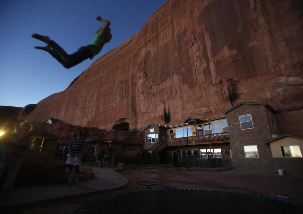 """Girls play on a trampoline near a home blasted from a rock wall at the Rockland Ranch community outside Moab, Utah, November 2, 2012. The """"Rock"""" as it is referred to by the approximately 100 people living there in about 15 families, was founded about 35 years ago on a sandstone formation near Canyonlands National Park. Polygamy was a part of the teachings of The Church of Jesus Christ of Latter-day Saints and was brought to Utah by faithful Mormons in the late 1840s. The mainstream Mormon church abandoned the practice in 1890, but an estimated 37,000 Mormon fundamentalists continue the practice today and believe plural marriage brings exaltation in heaven. Picture taken November 2, 2012. REUTERS/Jim Urquhart (UNITED STATES - Tags: RELIGION SOCIETY ENVIRONMENT TPX IMAGES OF THE DAY) - RTR3AEYA"""