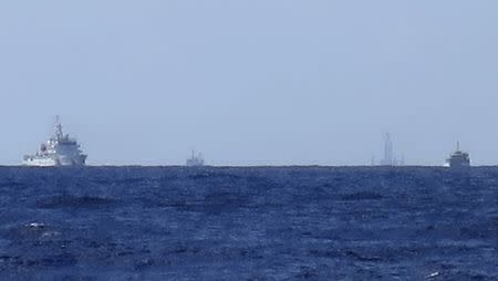 Chinese ships are seen on the horizon guarding the Haiyang Shiyou 981, known in Vietnam as HD-981, oil rig (2nd R) in the South China Sea, July 15, 2014. REUTERS/Martin Petty