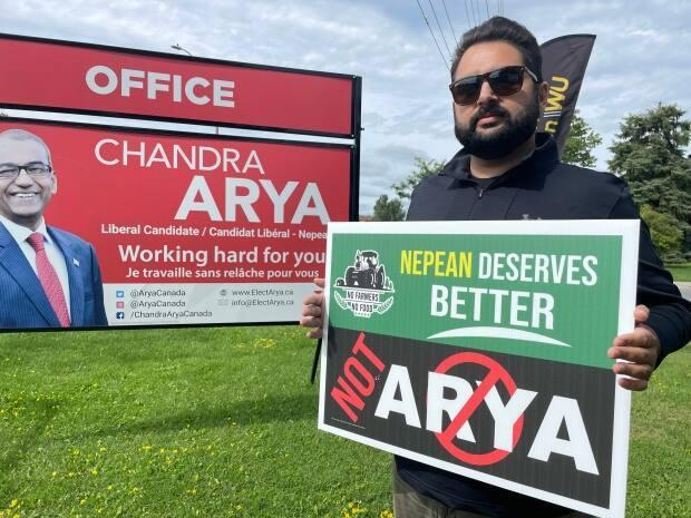 Vinny Manes, a member of the Ottawa Punjabi Association, holds up a sign that reads: 'Nepean deserves better, not Arya.' (Nicole Williams/CBC - image credit)