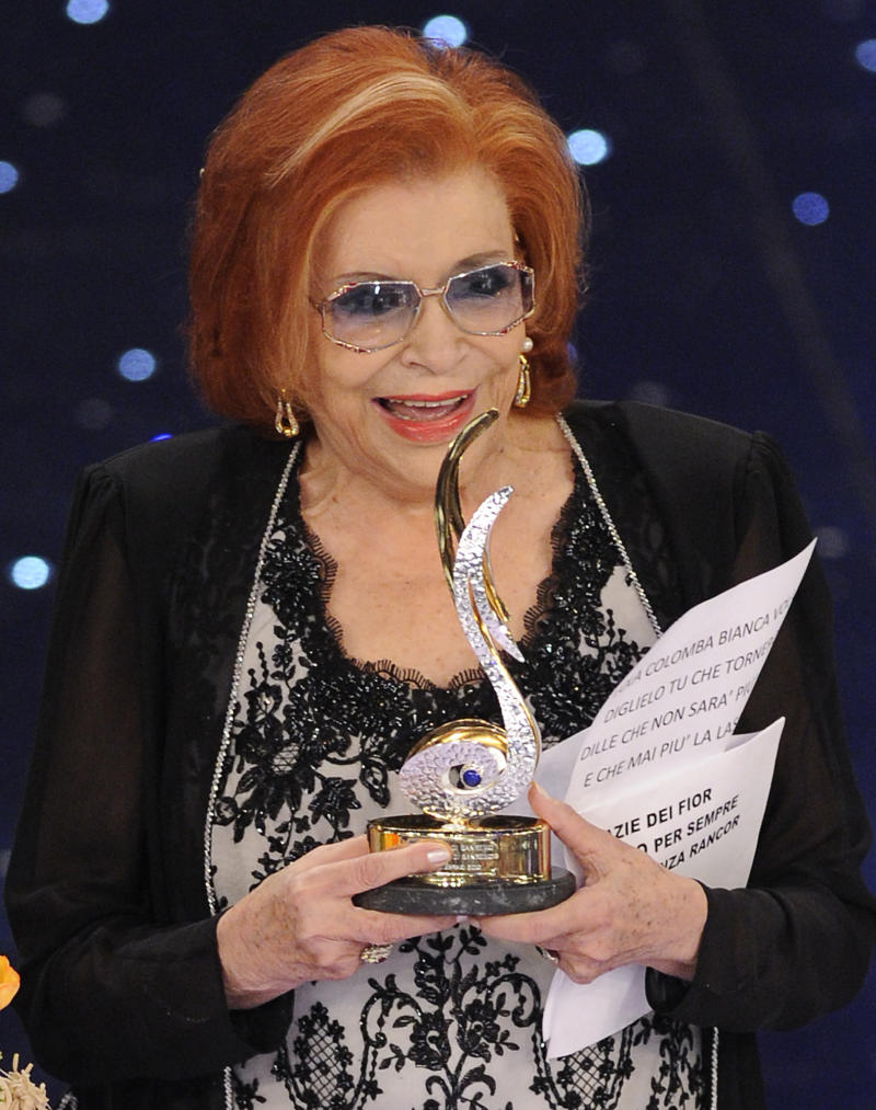 """FILE - In this Feb. 18, 2010 file photo Nilla Pizzi is honored with a prize for her career during the """"Festival di Sanremo"""" Italian song contest at the Ariston theater in San Remo, Italy. Nilla Pizzi, winner of the first San Remo festival, and whose voice was deemed too sensual to sing on radio during the fascist regime of Benito Mussolini, died on Saturday. She was 91, said RAI state TV, which broadcasts the week-long festival of Italian song each year. The Italian President Giorgio Napolitano in a condolence message hailed Pizza as a """"sensitive and popular interpreter of the Italian melodic tradition."""" During fascist rule in the years before World War II, Pizzi was kept away from radio work because her voice was deemed too """"modern, exotic and sensual,"""" the Italian news agency said. (AP Photo/Alberto Pellaschiar, File)"""