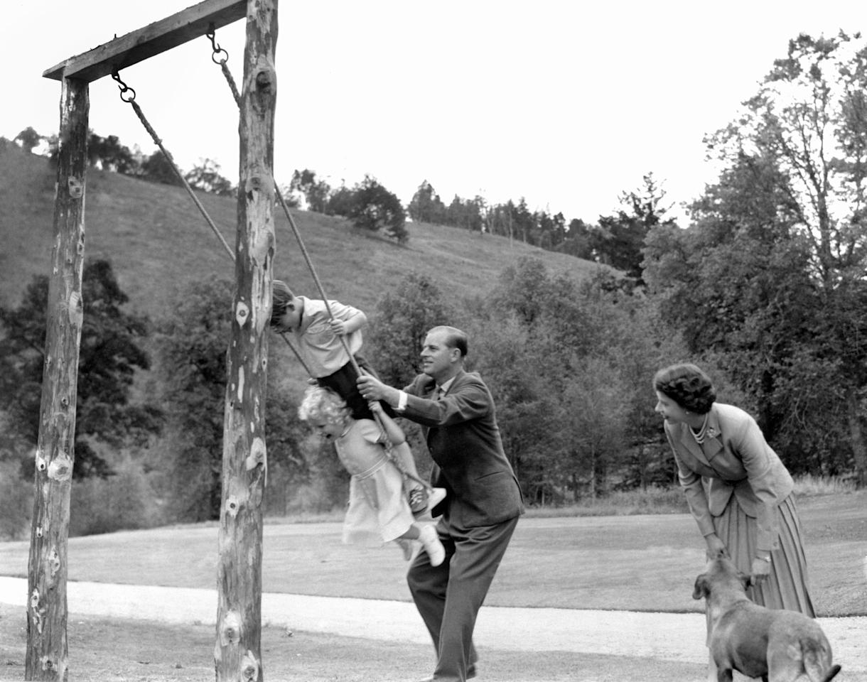 <p><span>The Duke of Edinburgh had his hands full keeping the lively Princess Anne and Prince Charles entertained as the Queen looked on in 1955 at Balmoral Castle. [</span>Photo: Getty Images.] </p>