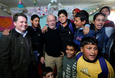FILE PHOTO: United Nations Children's Fund (UNICEF) Executive Director Anthony Lake (3rd L) stands with Justin Forsyth (L), chief executive of Save the Children, as they visit a school inside a refugee camp in Zahle, in the Bekaa Valley March 14, 2014. REUTERS/Mohamed Azakir/File Photo