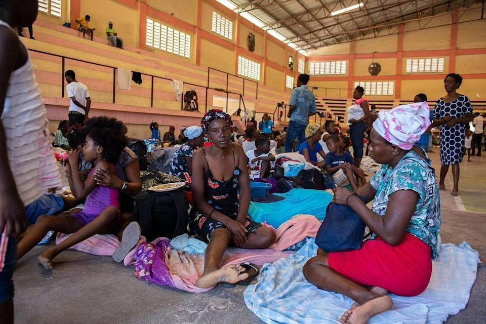 Internally displaced people sit inside a shelter at the Center Sportif of Carrefour in Port-au-Prince, Haiti, Tuesday, June 8, 2021. A UNICEF report says that escalating gang violence has displaced thousands of women and children in the capital in the first two weeks of June.