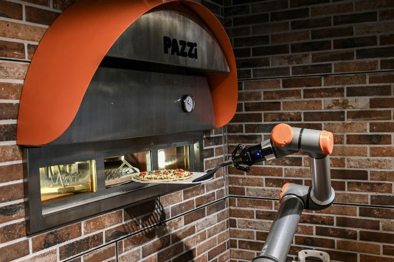 The glass-enclosed kitchen is staffed by silver robots that build, bake and box up pizzas with the help of specially developed equipment, at a rate of up to 80 an hour
