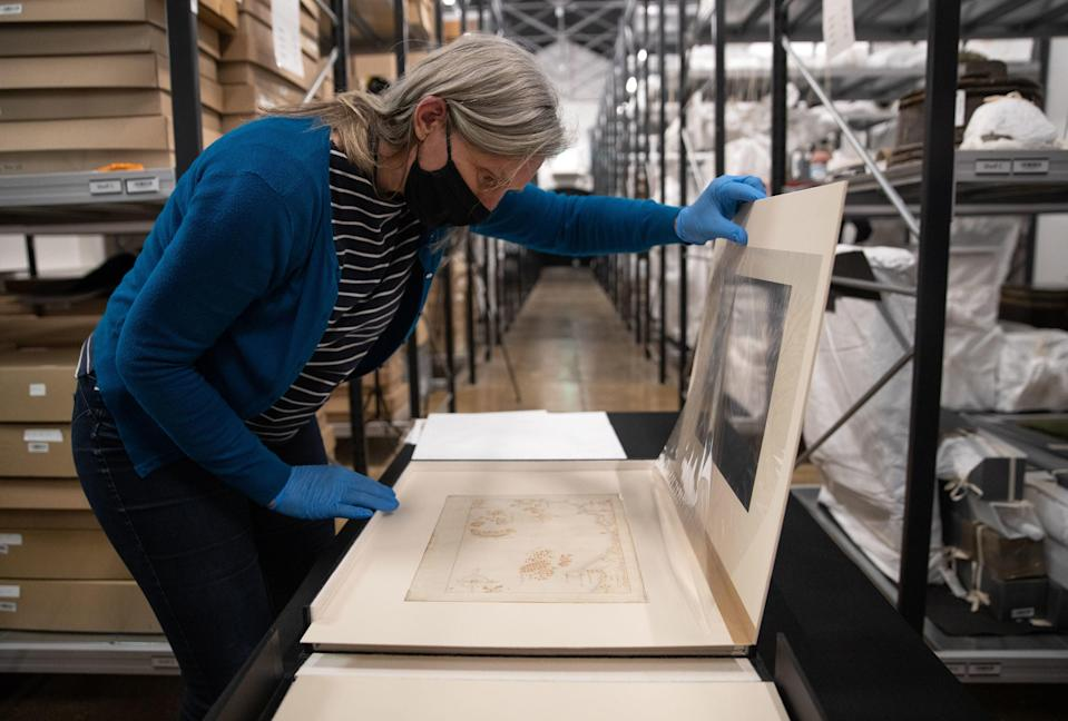 Victoria Ingles, senior curator at the National Museum of the Royal Navy, looks at one of the 'Armada Maps'PA