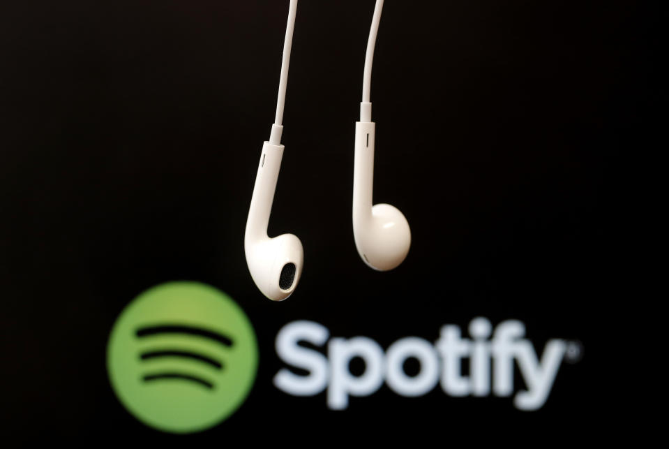 Headphones are seen in front of a logo of online music streaming service Spotify in this illustration picture taken in Strasbourg, February 18, 2014. Spotify is recruiting a U.S. financial reporting specialist, adding to speculation that the Swedish start-up is preparing for a share listing, which one banker said could value the firm at as much as $8 billion. REUTERS/Christian Hartmann (FRANCE - Tags: BUSINESS ENTERTAINMENT LOGO)