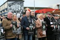 Relatives and supporters of the victims of the 1972 Bloody Sunday killings hold images of those who died as they march from the Bogside area of Derry