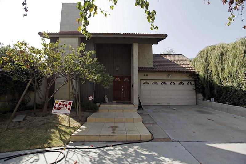 "This Tuesday, Sept. 25, 2012, photo shows a ""For Sale"" sign at the home of Nakoula Basseley Nakoula, the man who made the film ""Innocence of Muslims"" that has sparked violent protests, on a street in Cerritos, Calif. The filmmaker has received death threats and was forced into hiding after the 14-minute movie trailer rose to prominence. (AP Photo/Reed Saxon)"