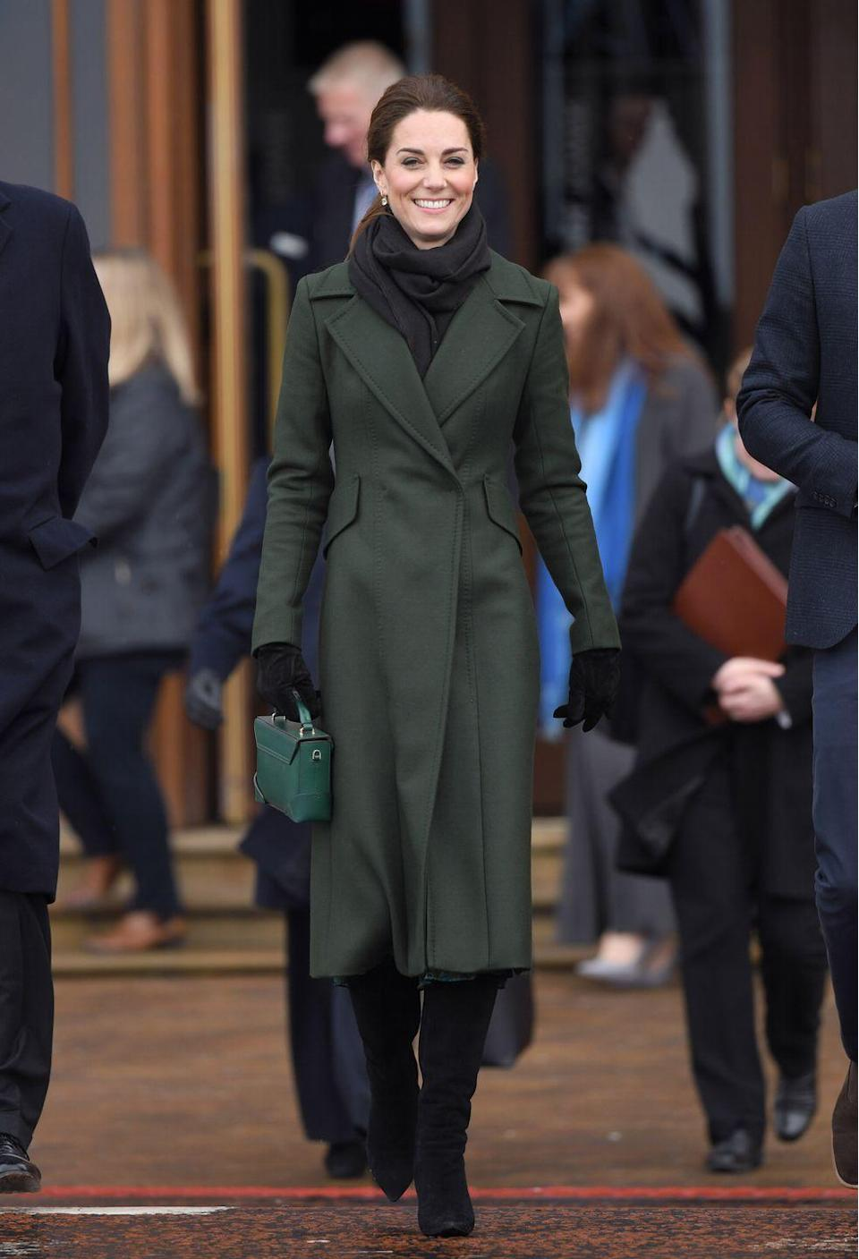 "<p>Kate Middleton sported a hunter green Sportmax coat, a black scarf and gloves, and high-heeled boots as she arrived in Blackpool. The duchess paired her look with her <a href=""https://www.shopbop.com/micro-bold-top-handle-bag/vp/v=1/1587486474.htm?extid=affprg_linkshare_SB-TnL5HPStwNw&cvosrc=affiliate.linkshare.TnL5HPStwNw&clickid=WHN0smWRpTHrSkY1saxx4y-tUkl0rp0S3Tvoys0&subid1=TnL5HPStwNw-Uc0lzrx6nexiHhEPCdAUtg&sharedid=42352"" rel=""nofollow noopener"" target=""_blank"" data-ylk=""slk:Manu Atelier"" class=""link rapid-noclick-resp"">Manu Atelier </a>suede top handle bag and small square drop earrings. </p><p><a class=""link rapid-noclick-resp"" href=""https://go.redirectingat.com?id=74968X1596630&url=https%3A%2F%2Fwww.shopbop.com%2Fmicro-bold-top-handle-bag%2Fvp%2Fv%3D1%2F1587486474.htm%3Fextid%3Daffprg_linkshare_SB-TnL5HPStwNw%26cvosrc%3Daffiliate.linkshare.TnL5HPStwNw%26clickid%3DWHN0smWRpTHrSkY1saxx4y-tUkl0rp0S3Tvoys0%26subid1%3DTnL5HPStwNw-Uc0lzrx6nexiHhEPCdAUtg%26sharedid%3D42352&sref=https%3A%2F%2Fwww.townandcountrymag.com%2Fstyle%2Ffashion-trends%2Fnews%2Fg1633%2Fkate-middleton-fashion%2F"" rel=""nofollow noopener"" target=""_blank"" data-ylk=""slk:Shop Similar""><strong>Shop Similar</strong> </a> <em>Micro Bold Top Handle Bag, Manu Atelier, $545</em></p><p><strong><a class=""link rapid-noclick-resp"" href=""https://go.redirectingat.com?id=74968X1596630&url=https%3A%2F%2Fwww.bloomingdales.com%2Fshop%2Fproduct%2Fkate-spade-new-york-square-leverback-earrings%3FID%3D1291641%26pla_country%3DUS%26cm_mmc%3DGoogle-PLA-ADC-_-Jewelry%2B%2526%2BAccessories-NA-_-Kate%2BSpade%2BNew%2BYork-_-98686397132USA%26CAWELAID%3D120156070001429841%26CAGPSPN%3Dpla%26CAAGID%3D47685645839%26CATCI%3Daud-298639203740%253Apla-384024108716%26CATARGETID%3D120156070006125192%26cadevice%3Dc%26gclid%3DCjwKCAiAwojkBRBbEiwAeRcJZMDr_eANnZbNvphConrPCBoiEGp46IPI6lrdcMSRHJvHsRI4Jxj9MBoCvUsQAvD_BwE&sref=https%3A%2F%2Fwww.townandcountrymag.com%2Fstyle%2Ffashion-trends%2Fnews%2Fg1633%2Fkate-middleton-fashion%2F"" rel=""nofollow noopener"" target=""_blank"" data-ylk=""slk:Shop Similar"">Shop Similar</a> </strong><em>Square Leverback Earrings, Kate Spade, $48</em></p>"